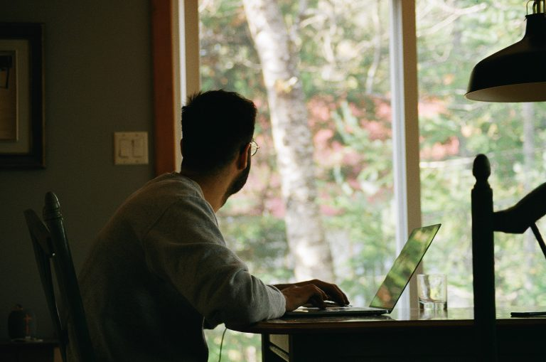 A man stares out of a window while sitting at a laptop